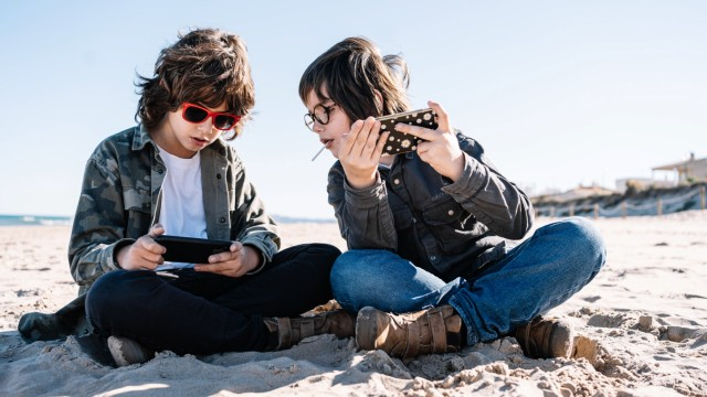 Two children playing with their mobile on the beach on a sunny winter day Copyright: xMikelxPoncex