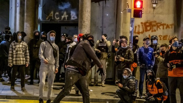 February 21, 2021, Barcelona, Catalonia, Spain: Protesters at Via Laietana throwing glass bottles at the police officer