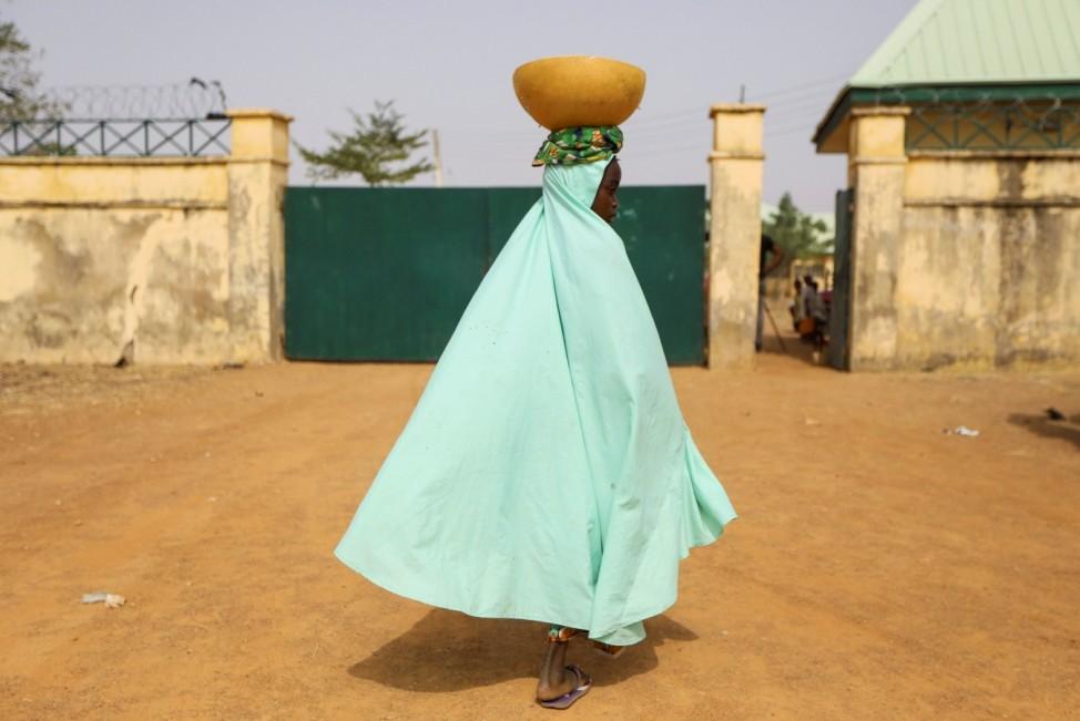 A milk maid walks toward the gate of JSS Jangebe school in Zamfara