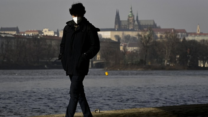 A man, wearing the respirator to prevent the spread of the coronavirus, walks during the sunny winter weather in Prague,