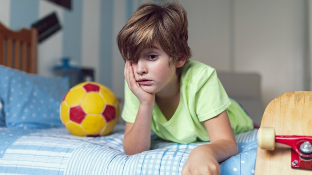 Bored little boy in casual clothes lying on bed near ball and skateboard unhappy with self isolation at home Copyright: