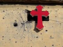 Mosul: Ein Kreuz an einer Wand mit Spuren von Einschlägen.