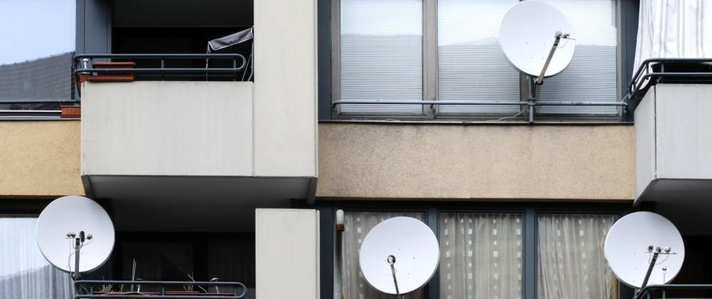Wohnhaueser in Berlin Blick auf ein Wohnhaus aus den 70er Jahren, an einigen Balkonen sind Satelittenschuesseln zum TV E