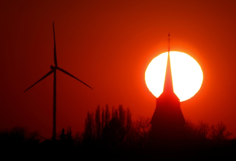 A power-generating windmill turbine and the church of Pronville-en-Artois village are pictured during sunset at a wind park near Cambrai
