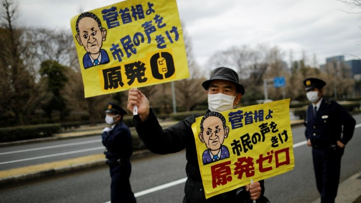 An anti-nuclear protester raises a placard during a rally in front of the parliament building in Tokyo