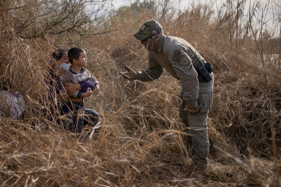 Asylum seeking migrants are asked to exit thick brush after crossing Rio Grande river into the U.S. from Mexico in Penitas, Texas