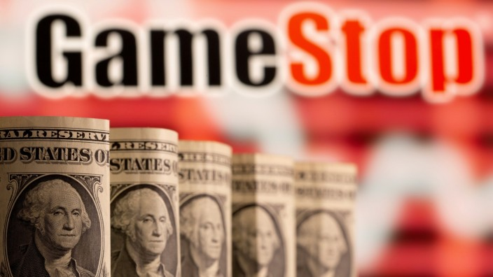FILE PHOTO: U.S. one dollar banknotes are seen in front of displayed GameStop logo