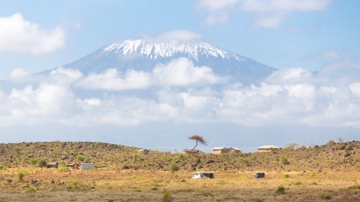 Kilimanjaro overlooking african savannah. Mount Kilimanjaro, Tanzania., the highest mountain in Africa. Traditional afri