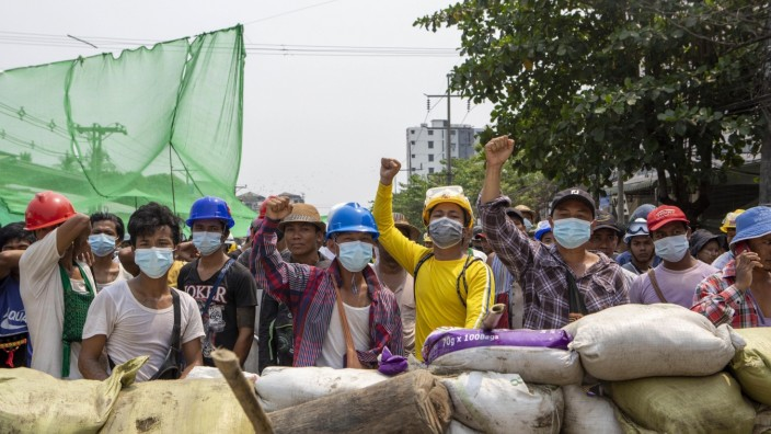 March 14, 2021, Yangon, Yangon, Myanmar: Protesters raise their fists from behind of the sand bags that block the road d