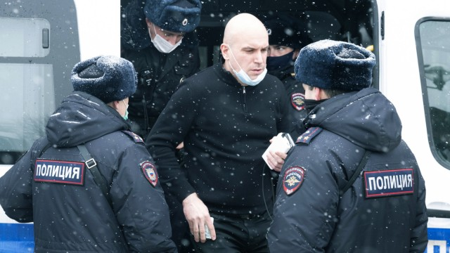 A man stands near a police bus after he was detained in Moscow, Russia, Saturday, March 13, 2021.