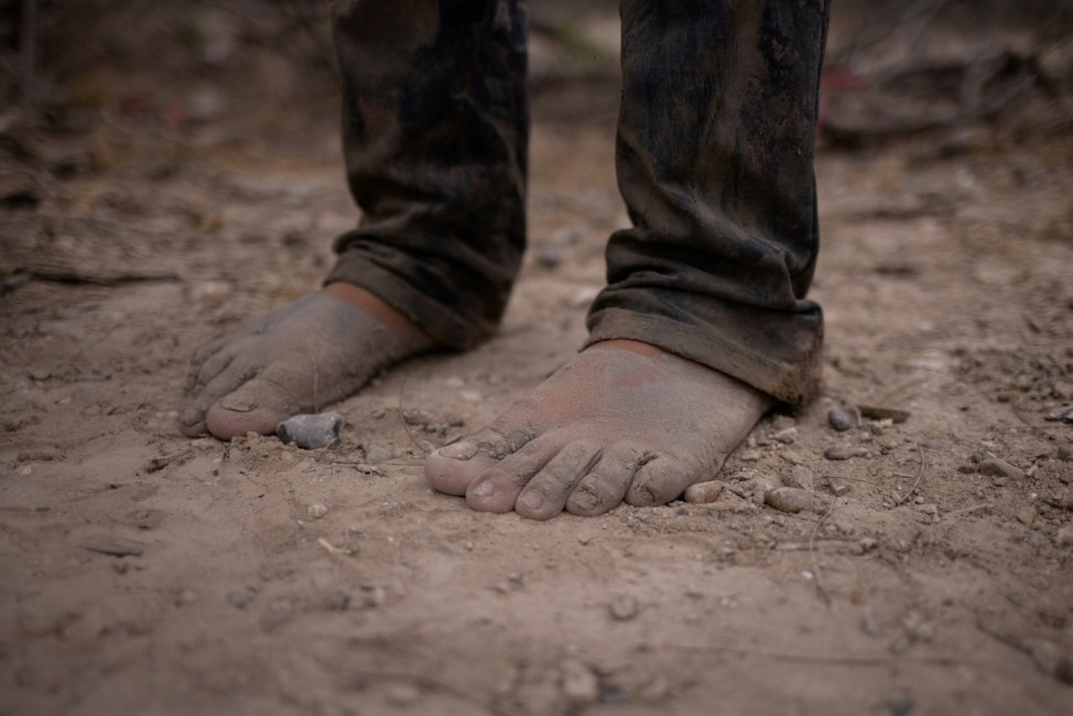 A migrant from Central America stands barefoot after crossing into the U.S. from Mexico on a raft in La Joya