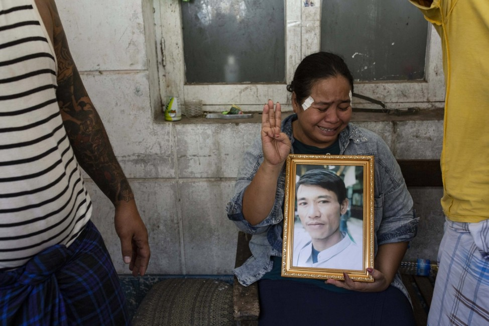 March 15, 2021, Yangon, Myanmar: A woman in tears makes the three finger salute while holding a portrait of her relative