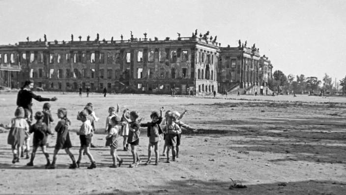 Potsdam Kindergärtnerin spielt mit ihrer Kindergruppe vor den Ruinen des Potsdamer Stadtschlosses nahe Berlins, Deutschl