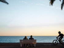 FRANCE - ON THE PROMENADE DES ANGLAIS On the famous Promenade des Anglais a couple sits on a bench, on one side a man ta