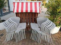 Zusammengestellte Stühle und ein geschlossener Strandkorb stehen an der Promenade von Timmendorfer Strand.