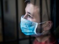 Trauriger Junge mit medizinischer Gesichtsmaske hinter einem Fenster während der Ausganssperre *** Sad boy with a medica