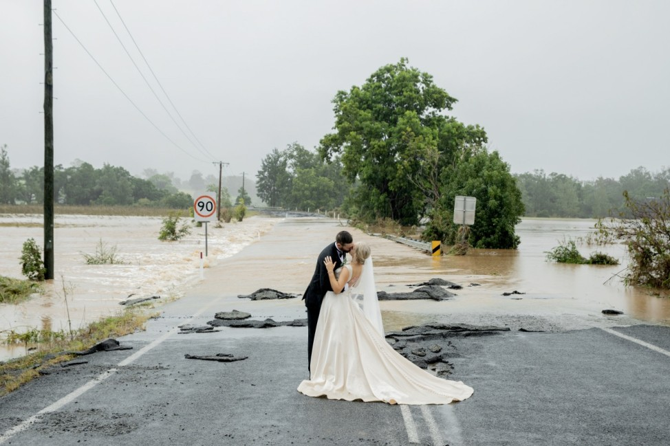 A stranded bride and groom rescued by helicopter on Saturday to get them to the church on time, kiss in front of a flooded bridge that had blocked their five-minute drive into town, in Port Macquarie, Australia in this picture obtained from social media