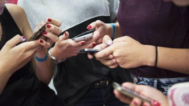 Social Media: Mädchen tippen auf ihren Smartphones