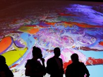 Visitors are seen in front of a painting by the British artist Sacha Jafri at the Atlantis hotel in Dubai
