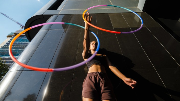 Low angle view of mixed race woman performing Hula Hoop dance in city Madrid, Madrid, Spain PUBLICATIONxINxGERxSUIxAUTxO