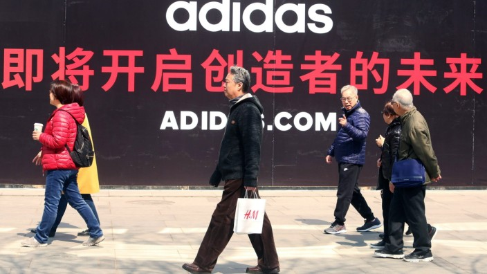 April 12 2018 Beijing China Chinese walk by a massive soon to open Adidas clothing store