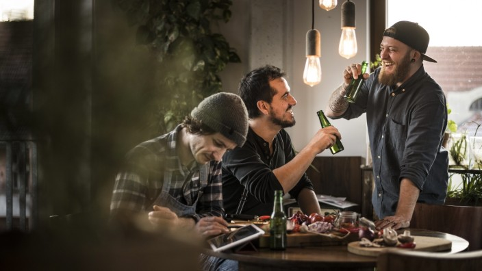 Friends drinking beer and eating together, what they have cooked model released Symbolfoto property released PUBLICATIO