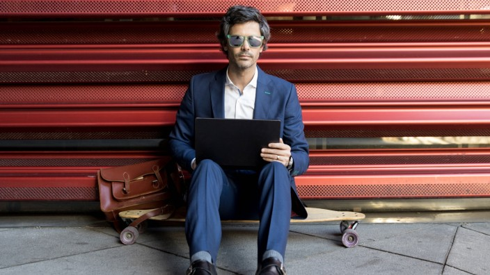 Smart businessman in elegant suit and sunglasses working on laptop comfortably placing on longboard leaning on metal red