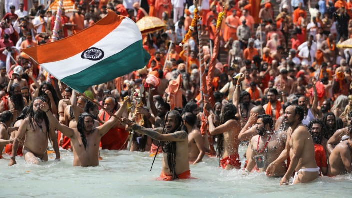 A Naga Sadhu waves the Indian flag as he takes a dip in the Ganges river during 'Kumbh Mela', or the Pitcher Festival, in Haridwar