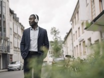 Young businessman listening music with headphones walking along the street model released Symbolfoto PUBLICATIONxINxGERx