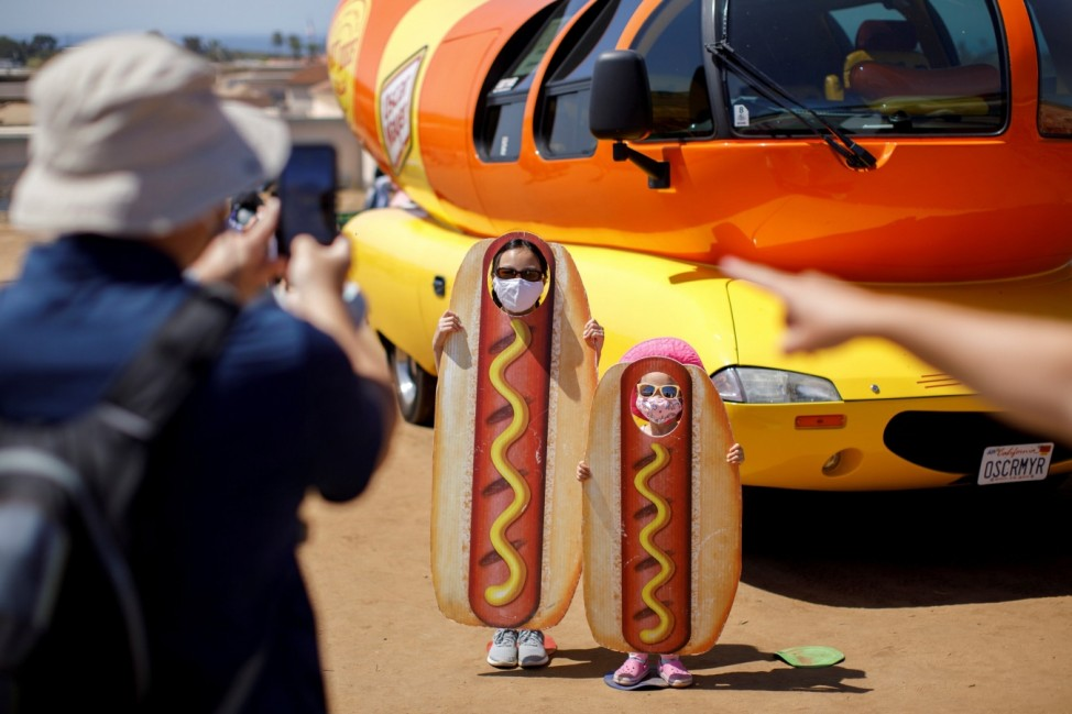 A family takes a picture at the Oscar Myer Wienermobile during a visit to 'The Flower Fields ' in Carlsbad