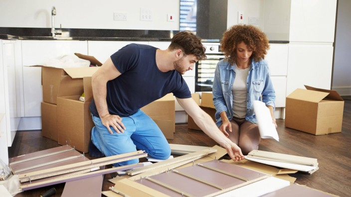 Couple Putting Together Self Assembly Furniture In New Home model released Symbolfoto property relea