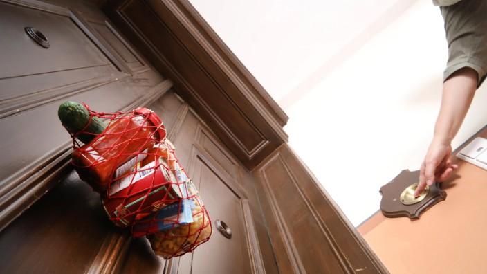 18.03.2020, Berlin - Deutschland. Nachbarschaftshilfe, Einkaufsnetz mit Lebensmitteln hängt an der Tür einer isolierten