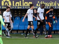 Valencia s French defender Mouctar Diakhaby (2-R) leaves the pitch with his teammates after allegedly receiving a racis; FC Valencia Spieler
