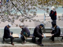 People play Chinese chess at a park under a cherry blossom trees near Bulgwangcheon Stream, in Seoul