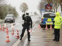 Ein Bundespolizist winkt in Aachen an der Grenze zu den Niederlanden ein Fahrzeug zur Überprüfung heran.