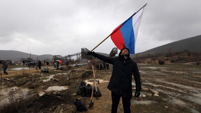CRIMEA, RUSSIA - MARCH 18, 2021: A man holds the Russian flag during an event marking the 7th anniversary of the reunifi