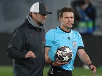 Liverpool s head coach Jurgen Kloop (L) talks to referee Felix Brych (R) at the end of the UEFA Champions League quarter; Brych