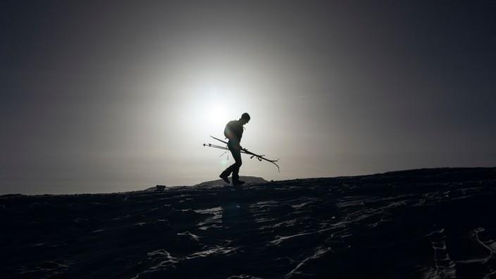 Ein Skifahrer trägt seine Ski