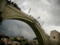 A man jumps off the newly rebuilt arch of 'Stari Most' (The Old Bridge) during the traditional diving competition in the southern Bosnian town of Mostar