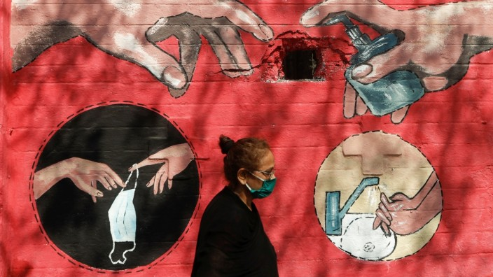 A woman walks past a graffiti, on a street, amidst the spread of the coronavirus disease (COVID-19) in Mumbai