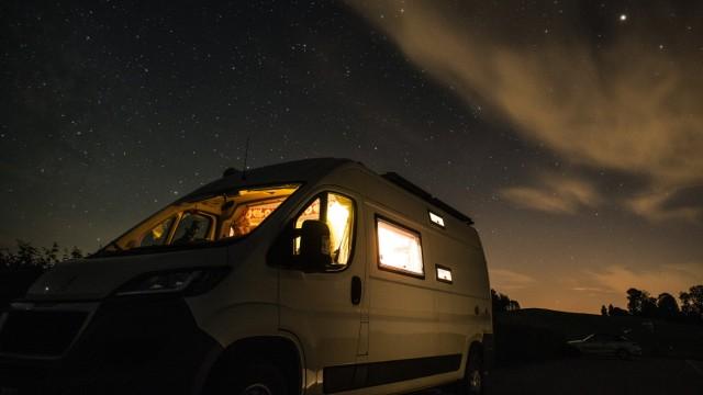 Ein Wohnmobil steht unter dem Sternenhimmel in einer klaren Neumondnacht auf einem Stellplatz bei Leutkirch, Baden Württ