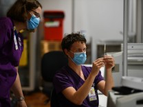 COMMUNITY COVID19 VACCINATION ROLLOUT, A healthcare worker is seen handling a AstraZeneca covid19 vaccination inside of