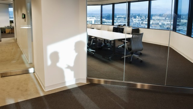 Shadows of two business people on the wall outside of a company conference room Shadows of two bus