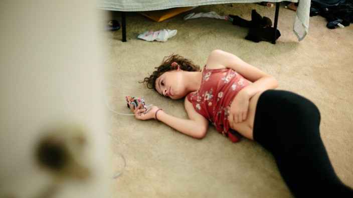 Teen girl lays on the carpeted floor of her room looking at her phone Thousand Oaks, CA, United States PUBLICATIONxINxGE
