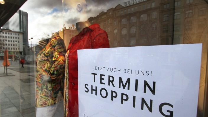 Schild mit Aufschrift Termin Shopping jetzt auch bei uns klebt im Schaufenster eines Modegeschäfts in der Innenstadt vo
