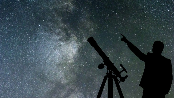 Milky Way. Night sky with stars and silhouette of a standing man with telescope. (Allexxandar)