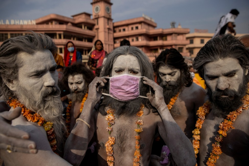 A Naga Sadhu, or Hindu holy man wears a mask before the procession for taking a dip in the Ganges river during Shahi Snan at 'Kumbh Mela', or the Pitcher Festival, amidst the spread of the coronavirus disease (COVID-19), in Haridwar