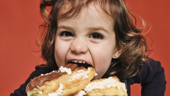 Closeup portrait of cheerful little girl enjoying sweet eclairs with chocolate while looking at camera against red back