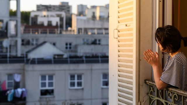 News Bilder des Tages FRANCE - SOCIETY - CONTAINMENT 8 p.m. in Montreuil, with her neighbours, a young woman applauds f