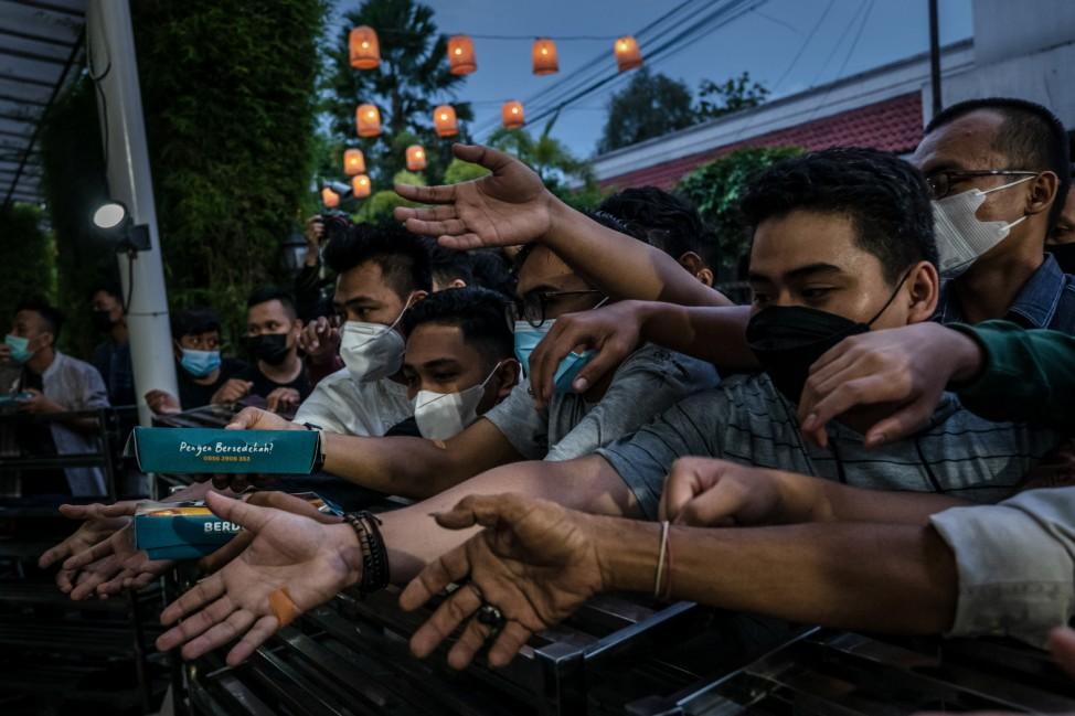 Ramadan: An der Jogokariyan-Moschee im indonesischen Yogyakarta nehmen Muslime nach Sonnenuntergang Essen entgegen, um damit das Fasten des ersten Tages im Ramadan zu beenden.